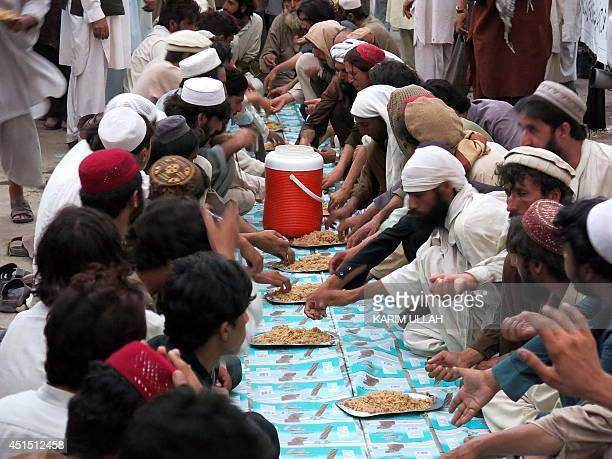 Internally displaced Pakistani civilians fleeing a military operation against Taliban militants in North Waziristan break their fast during the month...