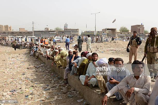 Internally displaced Pakistanis fleeing a military operation in the North Waziristan tribal agency wait in line outside a World Food Programme aid...