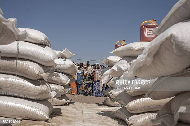 Internally displaced people at the Internally Displaced People camp, in Bama, on December 8, 2016 queue for food at a distribution point on on...