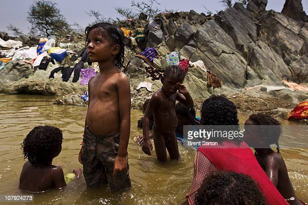 Internally displaced people bathe and wash clothes in a local river close to the AlMazraq IDP camps AlMazraq Yemen August 14 2010 A shaky ceasefire...