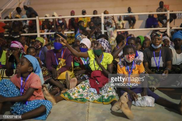 Internally displaced people from Palma gather in the Pemba Sports center to receive humanitarian aid in Pemba on April 2, 2021. - People were...