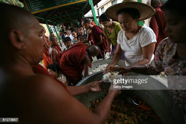 Internally displaced people line up for food distribution at a local Buddhist monastery May 13 in the village of Dalah at outskirts of Yangon Myanmar...