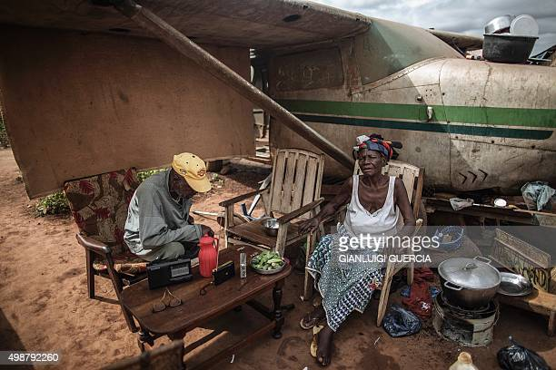 Internally Displaced People sit under the wreckage of a light plane at the Mpoko IDP camp in Bangui on November 26 ahead of a historical visit by the...