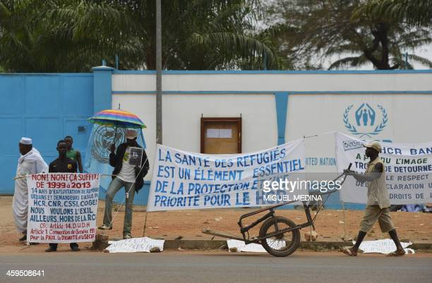Internally displaced people stand next to a sign reading 'The health of refugees is an essential element of protection and a priority for the HCR' as...