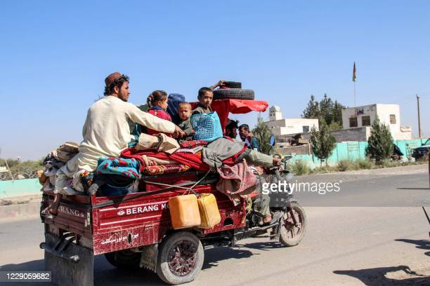 Internally displaced people with their belongings flee from Nadali district to Lashkar Gah during the ongoing clashes between Taliban fighters and...