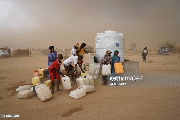 Internally displaced persons collect water in a brooding sandstorm Water is heavily rationed and is only available during onehour windows which...
