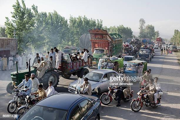 Internally Displaced Person's travel by road as they flee military operations in Swat Buner and Lower Dir on May 10 2009 in Malakand Pakistan...