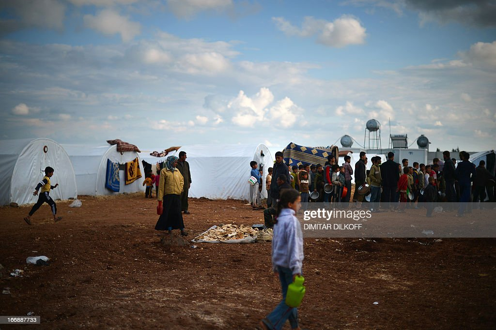 Internally displaced Syrian families wait for food distribution in the Maiber al-Salam refugee camp along the Turkish border in the northern province of Aleppo on April 17, 2013. UN agencies helping to care for the millions driven from their homes in Syria by two years of conflict warned that they face 'impossible' choices as funding fails to meet soaring needs. In all, some 1.3 million people have now fled Syria and some 200,000 more are crossing into neighbouring countries each month.