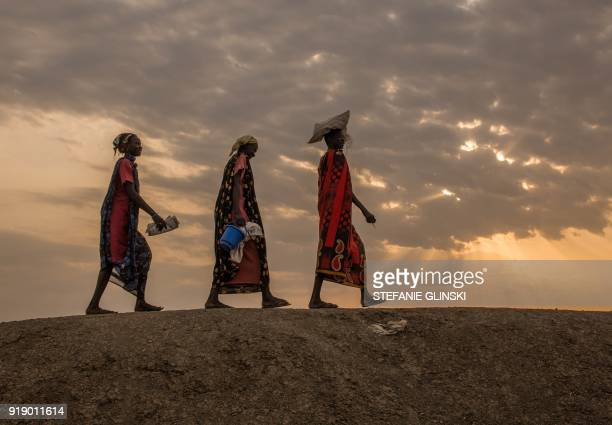 TOPSHOT Internally displaced women walk to a food distribution in the early morning at the Protection of Civilian site in Bentiu South Sudan on...