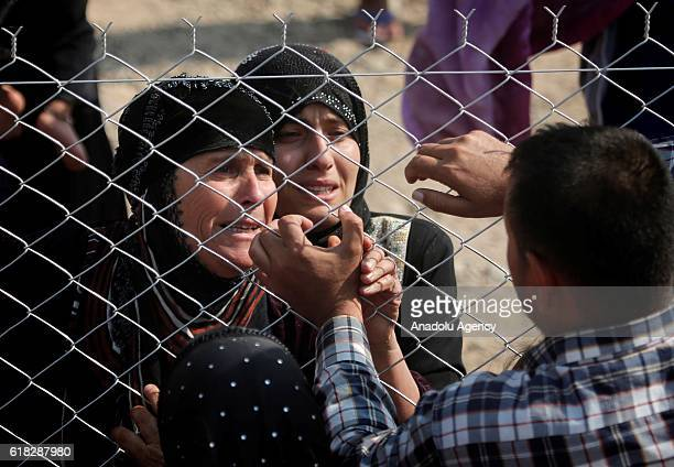 Internally relocated people fleeing the Topzava village of Hamdaniye district in Mosul due to Daesh meet their relatives behind wire clothes at Hazir...