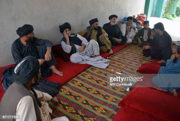 Internallydisplaced Afghan men and children who left their homes following a masskidnapping by suspected militants sit in a house after arriving from...