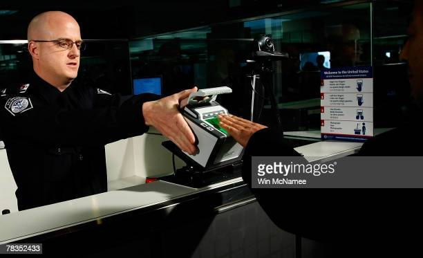 International airline passengers are fingerprinted on all ten fingers by US Customs and Border Protection officer Brian Pittack on arrival at Dulles...