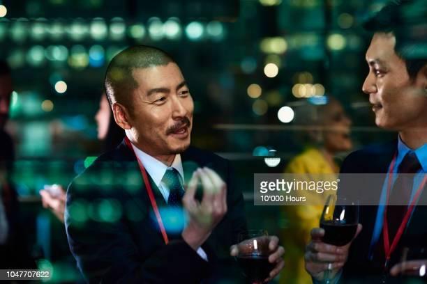 international businessmen socialising and drinking wine - überzeugen stock-fotos und bilder