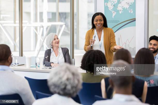 international businesswoman addresses audience during panel discussion - summit meeting stock pictures, royalty-free photos & images