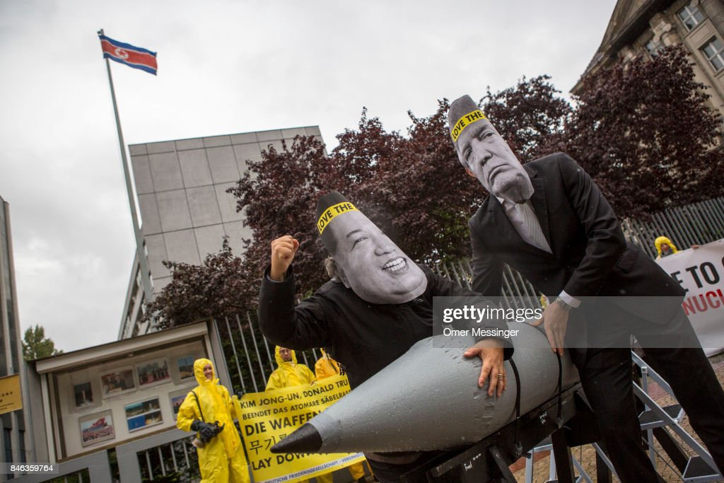 International campaign to abolish Nuclear Weapons (ICAN) activists wearing masks to look like US President Donald Trump and North Korean Kim Jong-Un carry a Styrofoam effigy of a nuclear bomb while protesting outside the North Korean Embassy on September 13, 2017 in Berlin, Germany. The protests, which were organized by anti-nuclear and pro-peace group ICAN, took place at both the North Korean and US embassies.