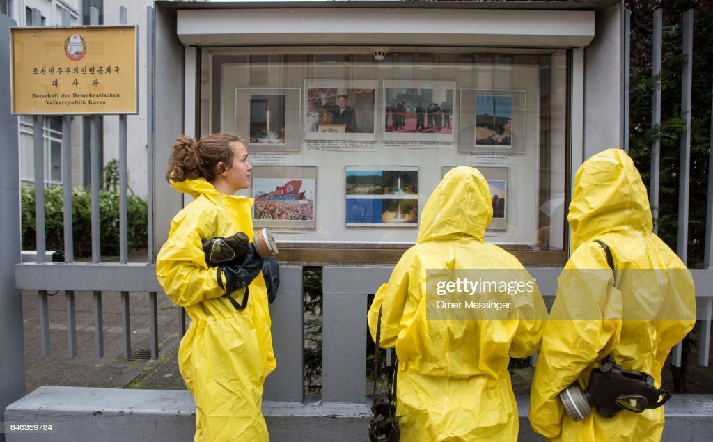 International campaign to abolish Nuclear Weapons (ICAN) activists wearing yellow hazard suits are seen looking at photos on a bulletin board of the North Korean Embassy on September 13, 2017 in Berlin, Germany. The protests, which were organized by anti-nuclear and pro-peace group ICAN, took place at both the North Korean and US embassies.