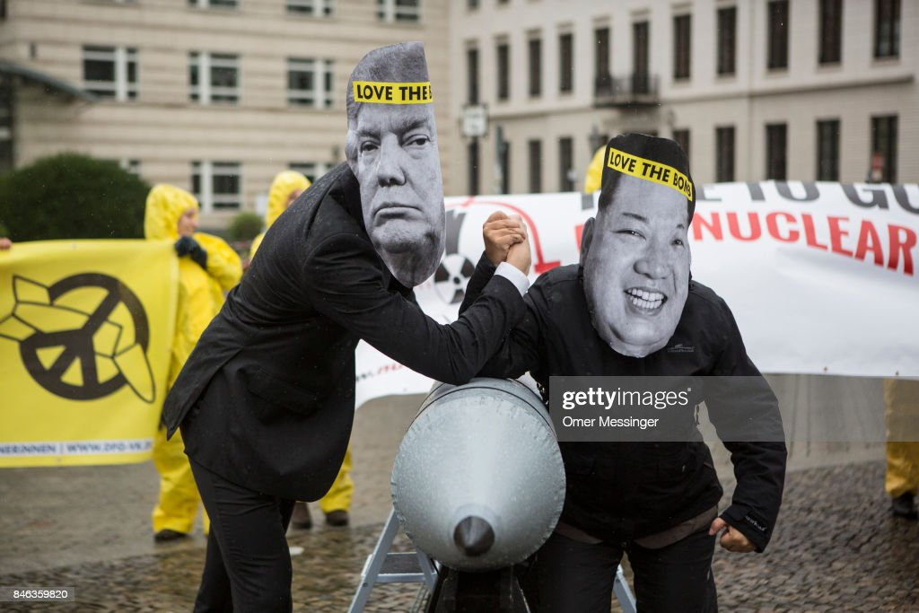 International campaign to abolish Nuclear Weapons (ICAN) activists wearing masks to look like US President Donald Trump and North Korean Kim Jong-Un pose next to a Styrofoam effigy of a nuclear bomb while protesting in front of the American Embassy on September 13, 2017 in Berlin, Germany. The protests, which were organized by anti-nuclear and pro-peace group ICAN, took place at both the North Korean and US embassies.