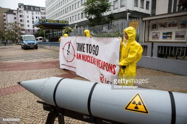 International campaign to abolish Nuclear Weapons activists wearing yellow hazard suits are seen next to a Styrofoam effigy of a nuclear bomb after...