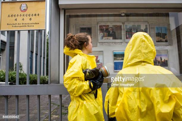 International campaign to abolish Nuclear Weapons activists wearing yellow hazard suits are seen looking at photos on a bulletin board of the North...