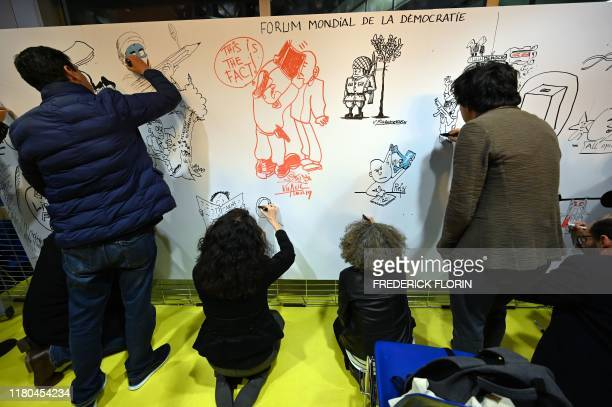 International cartoonists draws on a giant Peaces Fresco as part of the 2019 World Forum for Democracy at the Council of Europe in Strasbourg,...