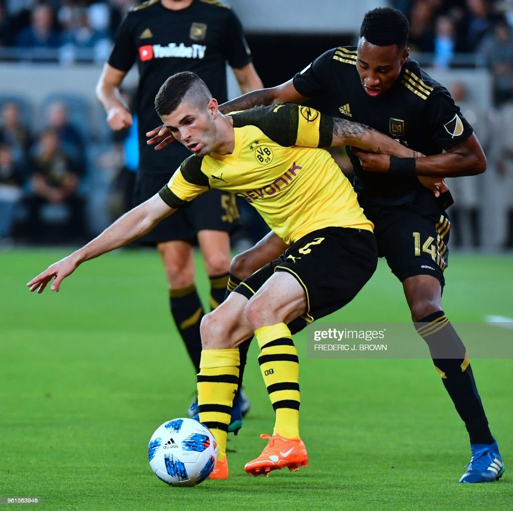 US international Christian Pulisic of Borussia Dortmund (L) vies for the ball with Mark-Anthony Kaye (R) of LAFC (Los Angeles Football Club) during their international soccer friendly in Los Angeles, California on May 22, 2018. - The game ended in a 1-1 draw.