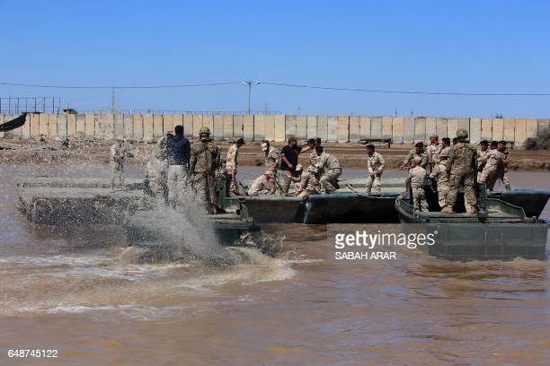 International coalition forces and Iraqi soldiers instal a floating bridge at the Taji camp north of Baghdad during a training session ahead of...