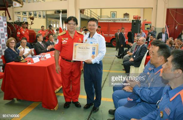 International Division Director of the Japan Firefighters Association Akimitsu Furumoto holds a certificate of commendation presented by Peru's...