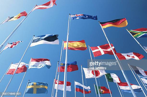 International flags blowing in wind, low angle view