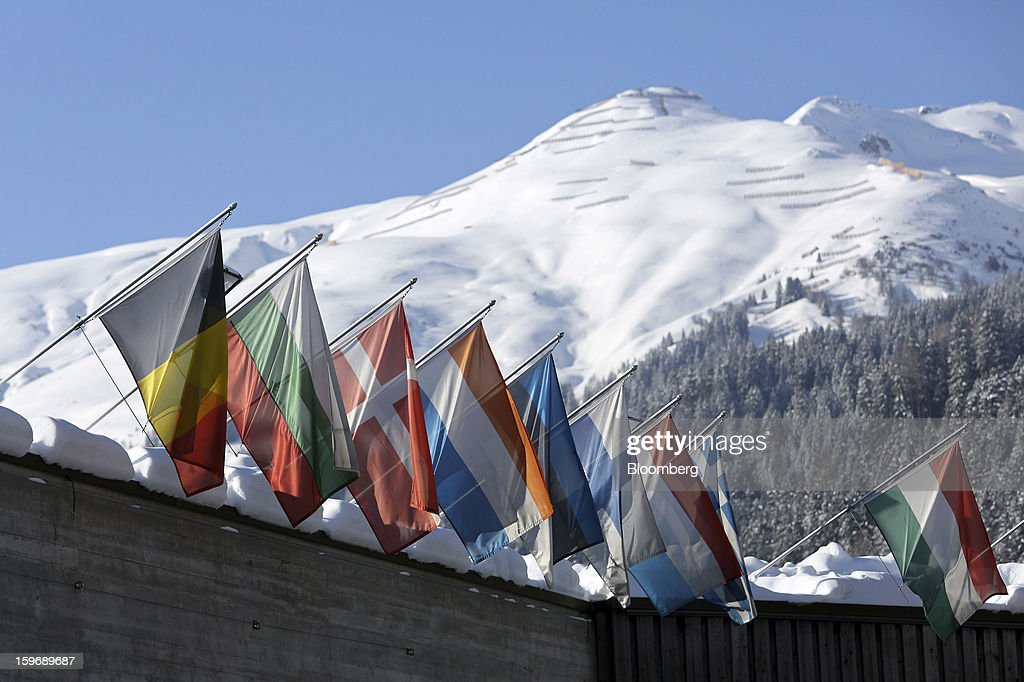 International flags fly above the Congress Centre, the venue of the World Economic Forum 2013, in Davos, Switzerland, on Friday, Jan. 18, 2013. Next week the business elite gather in the Swiss Alps for the 43rd annual meeting of the World Economic Forum in Davos, the five day event runs from Jan. 23-27. Photographer: Chris Ratcliffe/Bloomberg via Getty Images