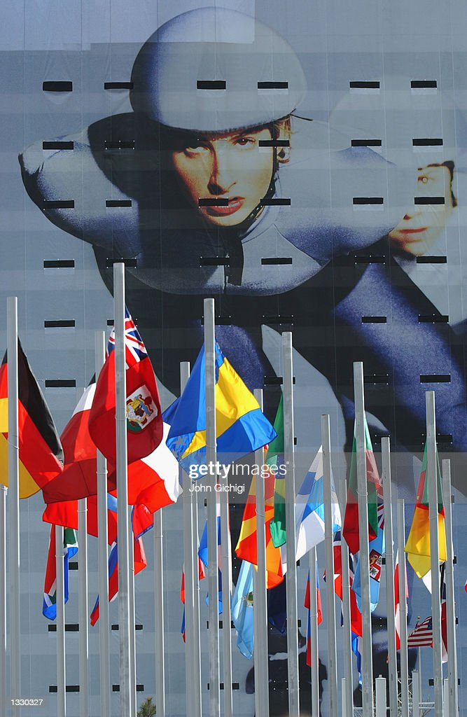 International flags wave in front of a building showing a speed skater banner before the medal awards ceremony at the Olympic Medals Plaza during the Salt Lake City Winter Olympic Games on February 24, 2002 in Salt Lake City, Utah.