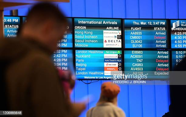 International flights arrivals are listed on a screen at Los Angeles International Airport on March 12, 2020 one day before a US flight travel ban...