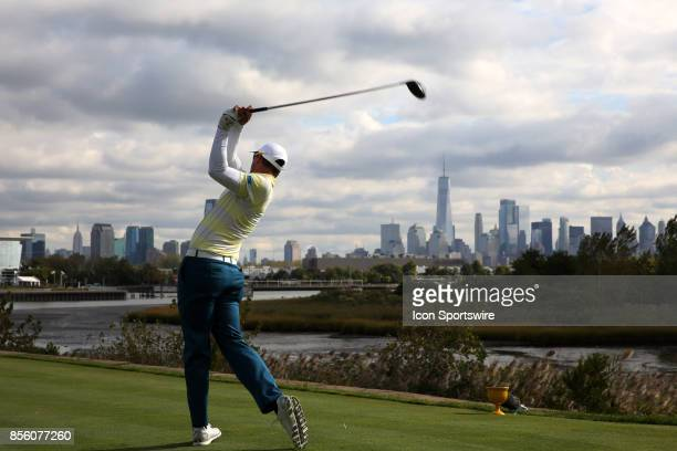 International golfer Adam Scott tees off on the 14th hole with the New York city skyline in the background during the third round of the Presidents...