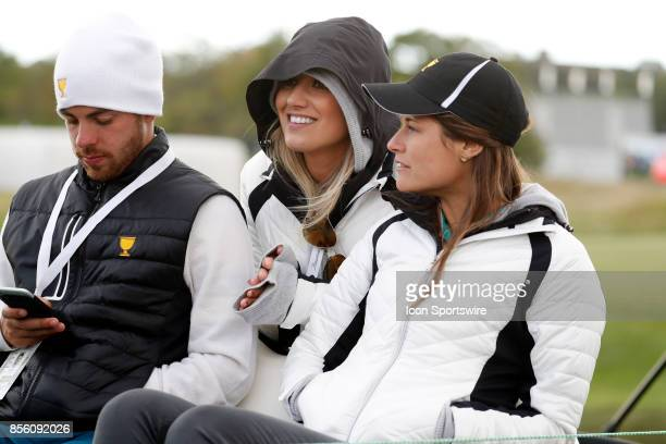 International golfer Jason Day's wife Ellie Day who is sitting in the middle of the golf cart tries to stay warm on the 17th hole during the third...