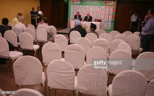 International Hockey Federation President Leandro Negre and FIH spokesman Arjen Meijer watch an almost empty press conference venue after journalists...