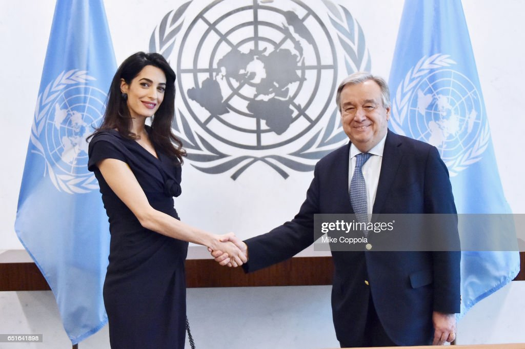 International Human Rights Lawyer Amal Clooney (L) and 9th Secretary-General of the United Nations António Guterres shake hands at United Nations Headquarters on March 10, 2017 in New York City.