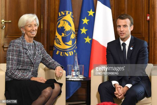 International Monetary Fund director Christine Lagarde speaks with French President Emmanuel Macron during the first day of a twoday conference on...