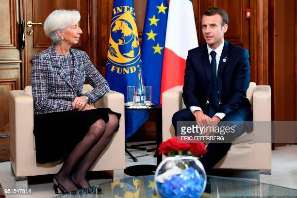 International Monetary Fund director Christine Lagarde speaks with French President Emmanuel Macron during the first day of a two-day conference on...