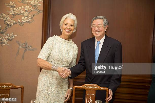 International Monetary Fund Managing Director Christine Lagarde is greeted by China's Central Bank Governor Xiaochuan Zhou on March 20 2016 in...