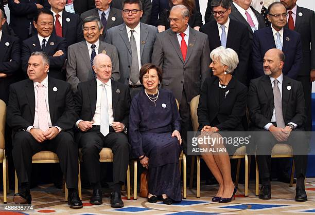 International Monetary Fund Managing Director Christine Lagarde smiles next to European Economic and Financial Affairs Commissioner Pierre Moscovici...