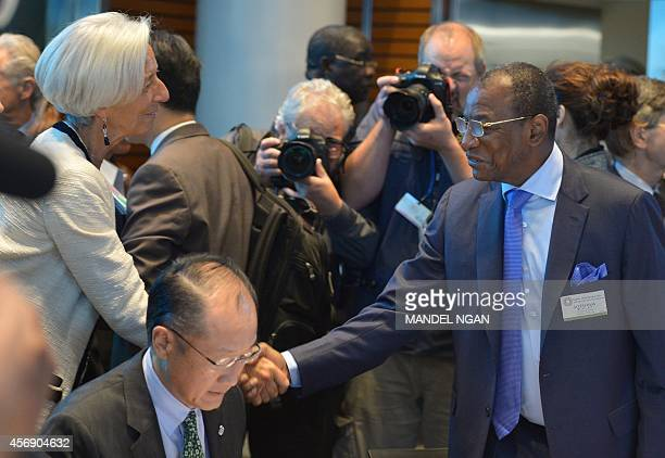 International Monetary Fund Managing Director Christine Lagarde shakes hands with Guinea President Alpha Conde as they arrive for a meeting on the...