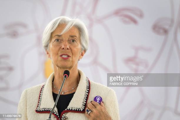 International Monetary Fund Managing Director Christine Lagarde shows a pin's she holds in solidarity whith a Swiss nationwide women's strike for...