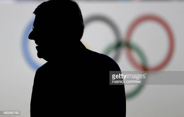 International Olympic Committee presidency candidate German lawyer and IOC VicePresident Thomas Bach is silhouetted against a logo of the Olympic...