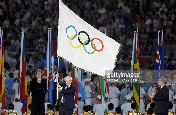 International Olympic Committee President Jacques Rogge looks on as London mayor Boris Johnson waves the Olympic flag at the National Stadium also...