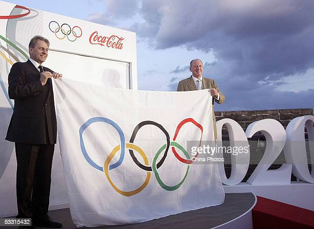 International Olympic Committee President Jacques Rogge presents a Fivering Olympic Flag to Neville Isdell chairman and CEO of the CocaCola Company...