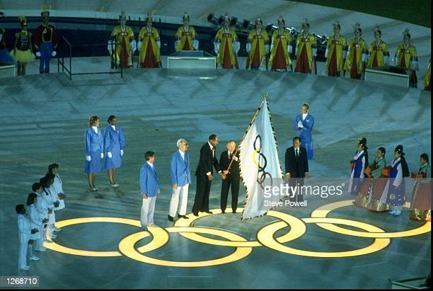 International Olympic Committee president Juan Antonio Samaranch and Los Angeles Mayor Tom Bradley hand over the official Olympic Antwerp flag to the...