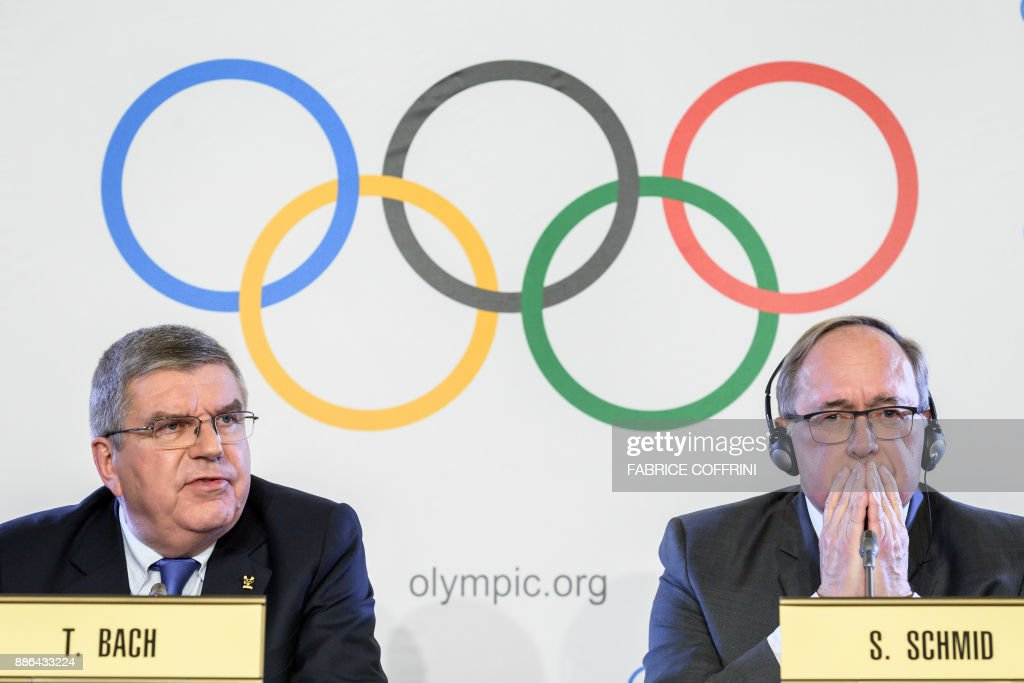TOPSHOT - International Olympic Committee (IOC) President Thomas Bach (L) and Chairman of IOC Inquiry Commission into alleged Russian doping at Sochi 2014 Swiss Samuel Schmid attend a press conference following an executive meeting on Russian doping, on December 5, 2017 in Lausanne. Russia were banned from the 2018 Olympics on December 5, over state-sponsored doping but the International Olympic Committee said Russian competitors would be able to compete 'under strict conditions'. / AFP PHOTO / Fabrice COFFRINI
