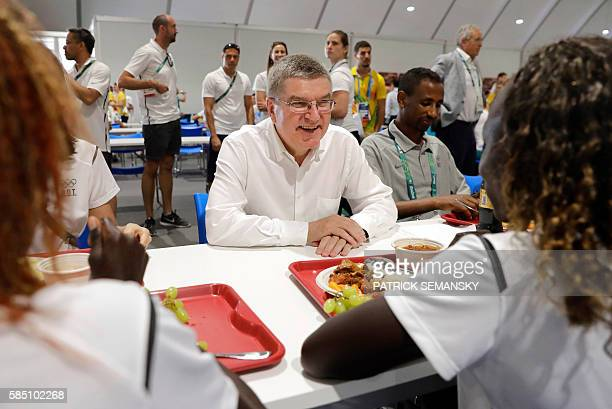 International Olympic Committee President Thomas Bach chats with members of the Refugee Olympic Team as they eat lunch at the athletes' village in...