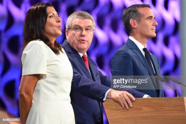 International Olympic Committee President Thomas Bach delivers a speech next to Paris Mayor Anne Hidalgo and Los Angeles Mayor Eric Garcetti during...