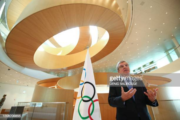 International Olympic Committee President Thomas Bach gestures as he speaks during an interview after the historic decision to postpone the 2020...