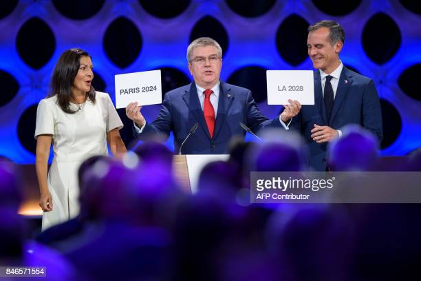 International Olympic Committee President Thomas Bach holds the cards bearing the name of Paris 2024 and Los Angeles 2028 next to both cities' mayors...